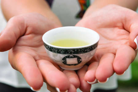 A small cup with yellow tea in the hands. Close-up. Asian tea Foto de archivo
