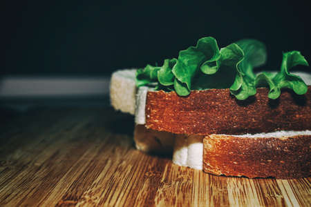 Two pieces of white bread and a leaf of lettuce on a wooden board. Kitchen theme. Healthy eating. Veganism Stockfoto