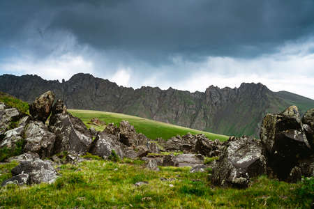 Stones on a green meadow against the backdrop of the Caucasus Mountains. Cloudy weather. Beautiful landscape