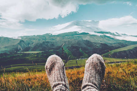 Legs in knitted gray woolen socks. Morning view on the Caucasus mountains to Elbrus. Travel lifestyle Beautiful landscape Stockfoto