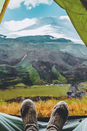 Legs in knitted gray woolen socks. Morning view from the tent on the Caucasus mountains to Elbrus. Travel lifestyle. Beautiful landscape Vertical photo