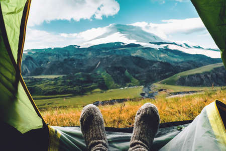 Legs in knitted gray woolen socks. Morning view from the tent on the Caucasus mountains to Elbrus. Travel lifestyle. Beautiful landscape