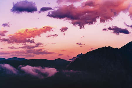 Purple-pink sky with clouds over the silhouette of the Caucasus Mountains Sunset landscape