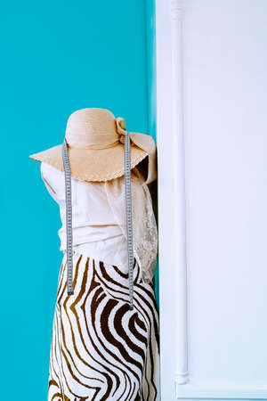 Fashion design mannequin with fabrics, measuring tape and hat. Vertical photo