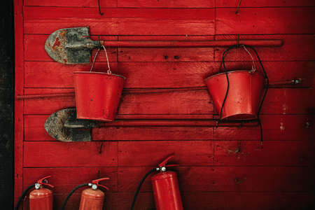 Fire extinguishing tools. Shovels, buckets, fire extinguishers on a red wall Stockfoto