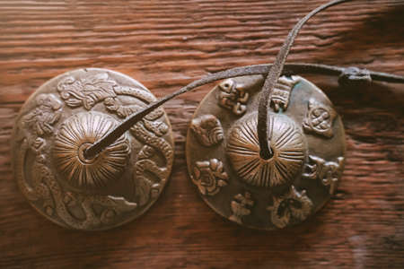 Indian Traditional Musical Instruments for kirtan bronze karatals. object for religious rituals, meditations and alternative medicine. Tibetan temple bells on wooden background Stockfoto