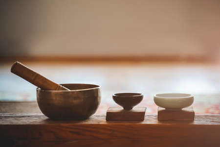 Tibetan bronze singing bowl for meditation and mindfulness. Little cup of tea on on a wooden surface