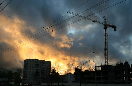 Reinforced steel & concrete building under construction. Safety guard rails, flyforms and tower crane at sunset photo