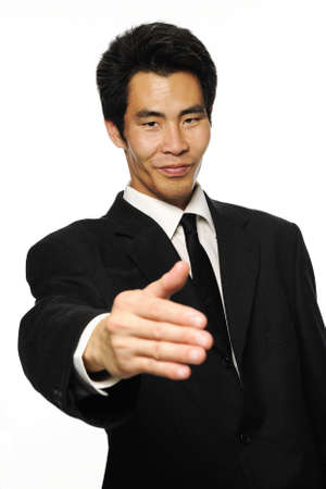 Businessman in black suit wants to shake your hand against white background photo