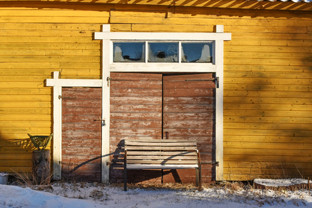 Old yellow barn with brown door Stock Photo