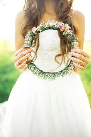 bride in wedding dress holding a wreath of lights in the hands 版權商用圖片