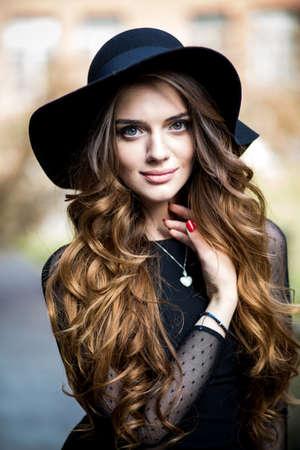 capelli lunghi: giovane donna bella elegante (ragazza) in abito e cappello