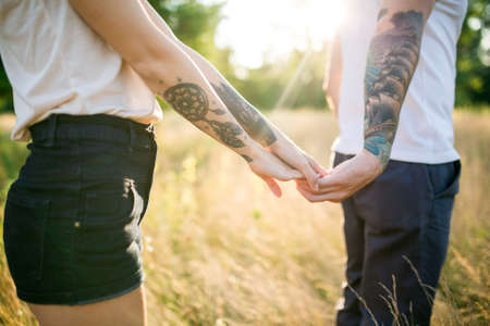 A man and a girl with a tattoo on the nature holding hands 版權商用圖片