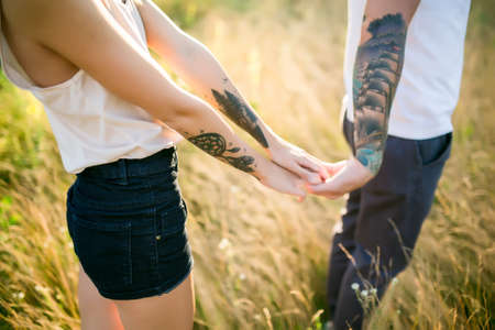 two women: A man and a girl with a tattoo on the nature holding hands Stock Photo