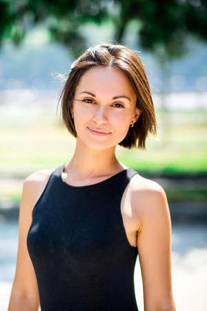 gente adulta: hermosa joven morena con un vestido negro con una sonrisa dulce y gran aspecto gráfico que presenta a la cámara Foto de archivo