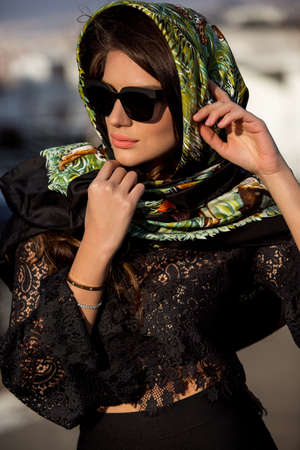 beautiful brunette girl in a headscarf and sunglasses. Stylish and luxury model