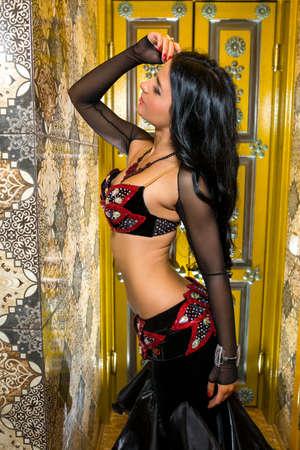 mujeres fashion: mujer joven hermosa danza del vientre en el vestido de traje rojo y negro precioso. Hermosa morena con una excelente figura y plásticos corporales Foto de archivo