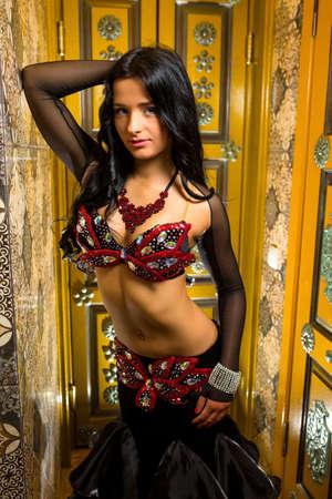 mooie vrouwen: Mooie buikdanseres jonge vrouw in prachtige rode en zwarte kleding kostuum. Mooie brunette met een uitstekend figuur en lichaam plastics Stockfoto