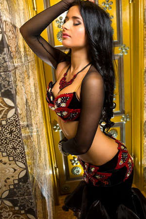 Beautiful belly dancer young woman in gorgeous red and black costume dress. Beautiful brunette with an excellent figure and body plastics