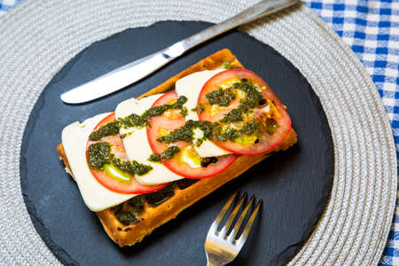melted cheese: Belgian waffle with sauce, melted cheese and tomatoes with herbs