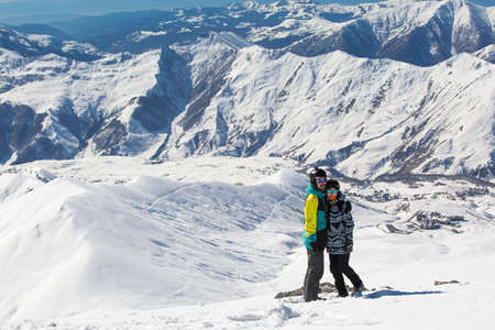 Couple in love snowboarder snowboarding on fresh white snow on ski slope on Sunny winter day Stock Photo