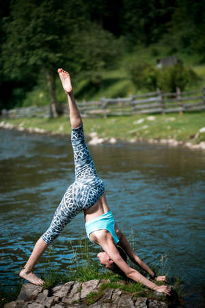 nice body: Young beautiful girl with nice body stands on the head during yoga on the shore of a mountain river.