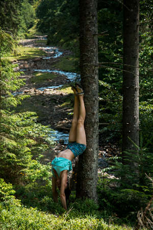nice body: Young beautiful girl with nice body stands on the head during yoga in the forest on the nature Stock Photo