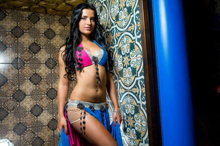 Beautiful belly dancer young woman in gorgeous pink and blue costume dress. Beautiful brunette with an excellent figure and body plastics