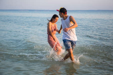 out of date: Young couple running on beach holding hands and laughing at sunset out to sea. The concept of love and fun, a date Stock Photo