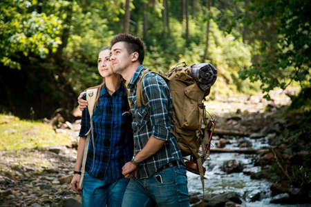Man and woman tourists walking hand in hand through the woods in the mountains Stock Photo