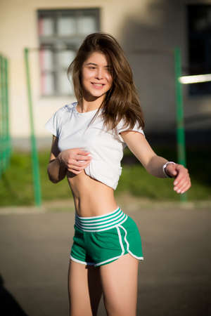 Beautiful young brunette girl doing sport outdoors in summer