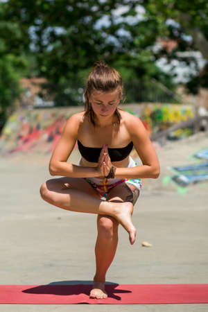 rive: Young beautiful girl with nice body does yoga on the nature.