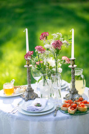 formal dinner party: Elegant beautiful decorated table with meals and tableware at wedding reception closeup