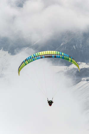 Parachute sky-diver flying in clouds above mountains with fresh snow on Sunny winter day in the ski resort. Travel adventure concept. space for text