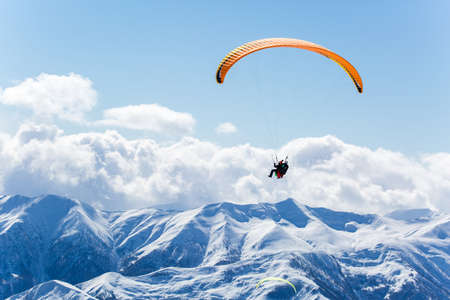 parachute jump: Parachute sky-diver flying in clouds above mountains. Travel adventure concept. space for text