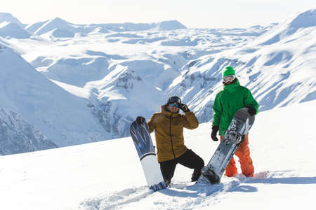 snowboarder snowboarding on fresh white snow with ski slope on Sunny winter day Stock Photo