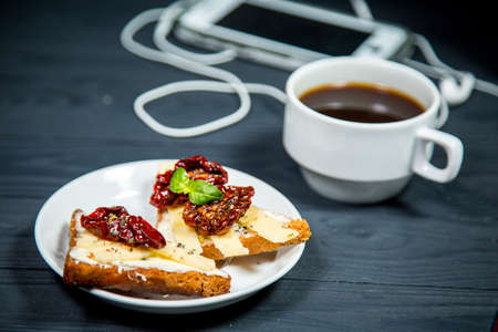 Beautiful background with Cup of coffee and toast with sun-dried tomatoes, a mobile phone with headphones on wooden table. The concept of a healthy lunch, business people