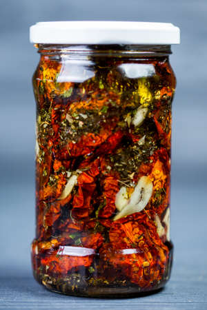sun-dried tomatoes with olive oil and spices in a jar Stock Photo