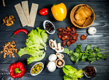 Sun-dried tomatoes with a salad, mushrooms, nuts, toast, diet bread, pepper, olives, Basil n wooden background