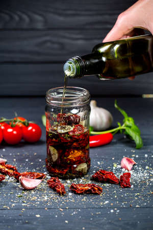 sun-dried tomatoes with olive oil and spices the cooking process of kanawati, female hand falls asleep ingredients in a jar on wooden background
