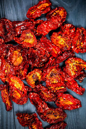 sun-dried tomatoes with olive oil and spices on wooden background