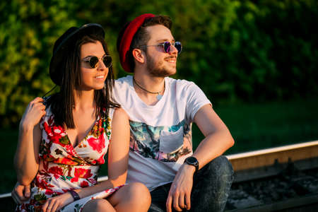 Young couple in love sitting on railroad together