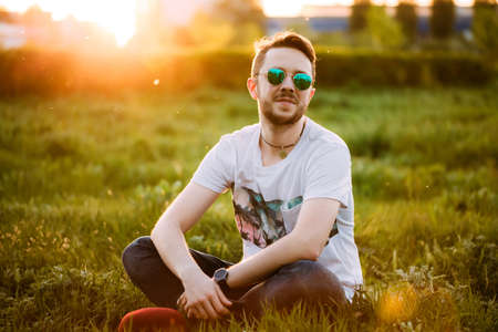 Portrait of a young handsome man outdoors in sunglasses on meadow background 版權商用圖片