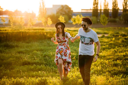 Couple in love having fun and laughing. The guy walking with his girlfriend. A man and a woman in sunglasses relaxing outdoors. 版權商用圖片