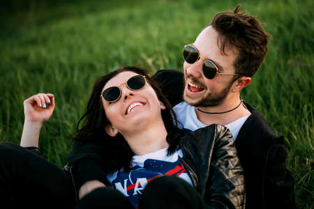 The guy walking with his girlfriend. A man and a woman in sunglasses with a beautiful smile outdoors. Loving couple laughing and having fun relaxing