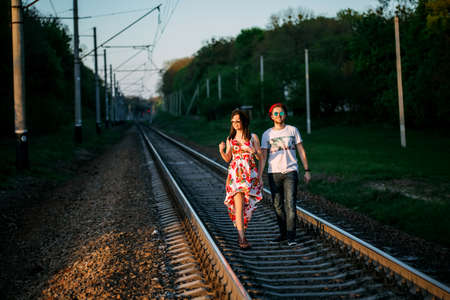 Young couple in love walking on railroad together 版權商用圖片