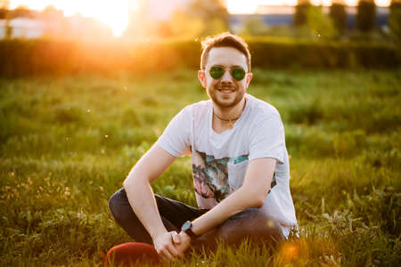 Portrait of a young handsome man outdoors in sunglasses on meadow background Stok Fotoğraf