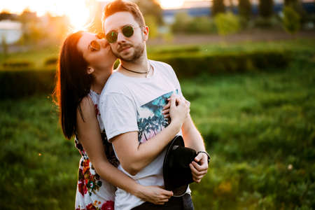 Couple in love kissing. The guy walking with his girlfriend. A man and a woman in sunglasses relaxing outdoors.