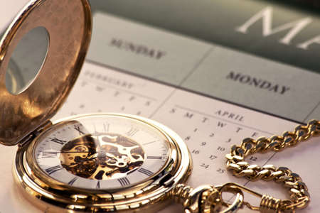 hands in  pocket: Close up of a gold pocket watch on a calendar Stock Photo