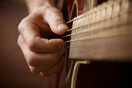 guitarra acustica: Cierre de la mano del guitarrista tocando guitarra ac�stica Foto de archivo